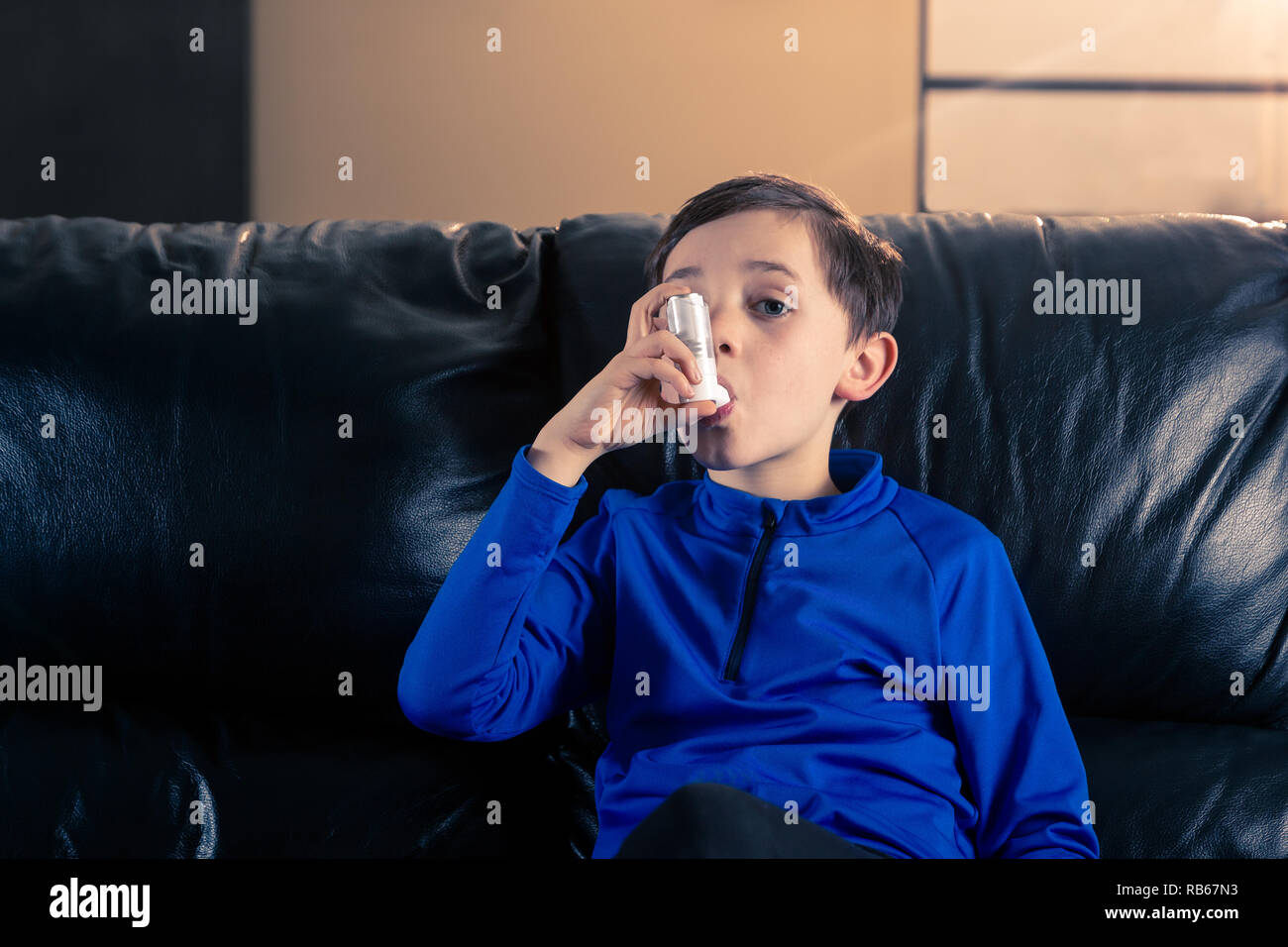 8 year old boy wearing sportive clothing using an asthma inhaler sitting in sofa. Concepts : health, illness, doping - Stock Image