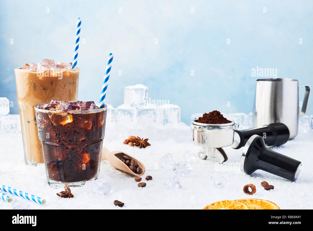 Summer drink iced coffee in a glass and ice coffee with cream in a tall glass surrounded by ice, coffee beans, portafilter, tamper, milk jug and vario Stock Photo