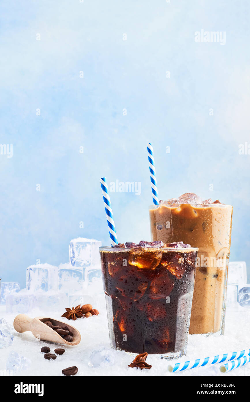 Summer drink iced coffee or soda in a glass and ice coffee with cream in a tall glass surrounded by ice cubes, coffee beans and various spices on snow Stock Photo