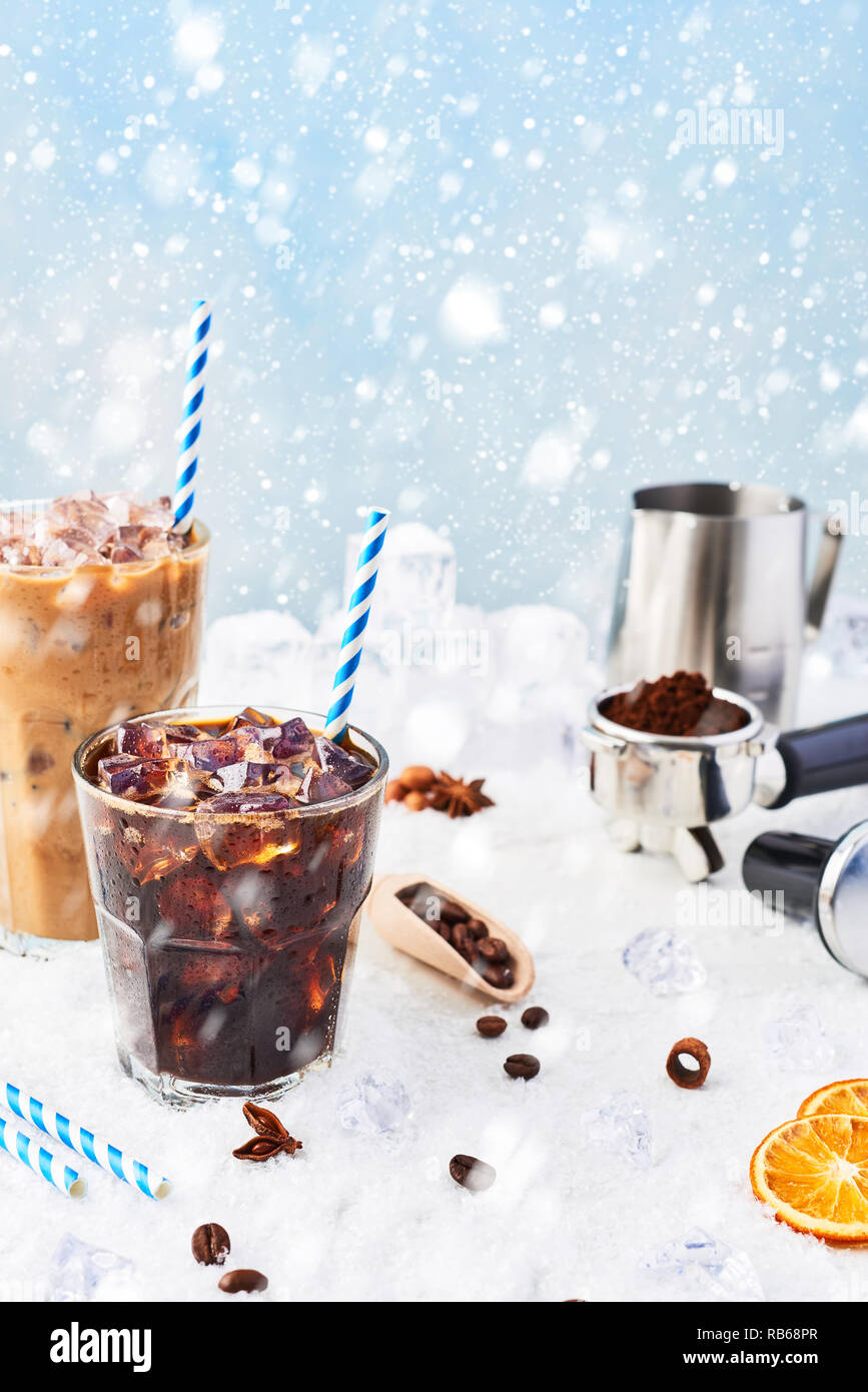 Winter drink iced coffee in a glass and ice coffee with cream in a tall glass surrounded by ice, coffee beans, portafilter, tamper, milk jug and vario Stock Photo