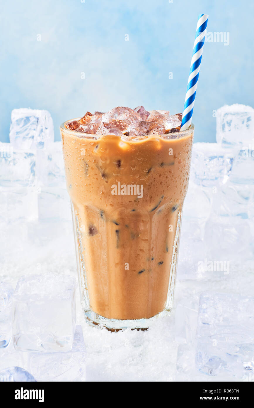 Summer drink ice coffee with cream in a tall glass with droplets and straw surrounded by ice cubes on snow over blue background. Selective focus, copy Stock Photo