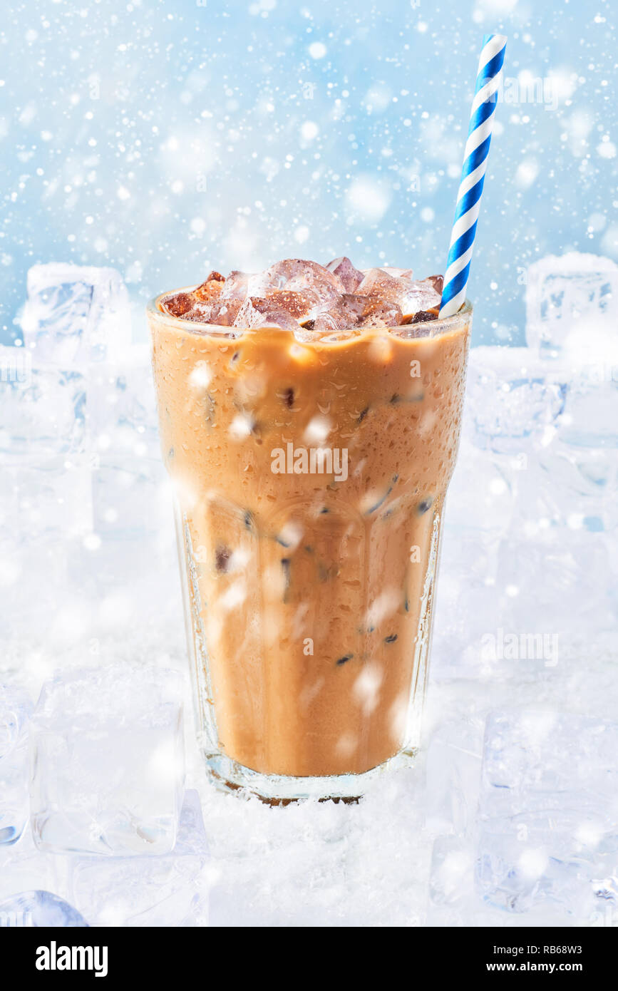 Winter drink ice coffee with cream in a tall glass with straw surrounded by ice cubes on snow over blue background with snow. Selective focus, copy sp Stock Photo