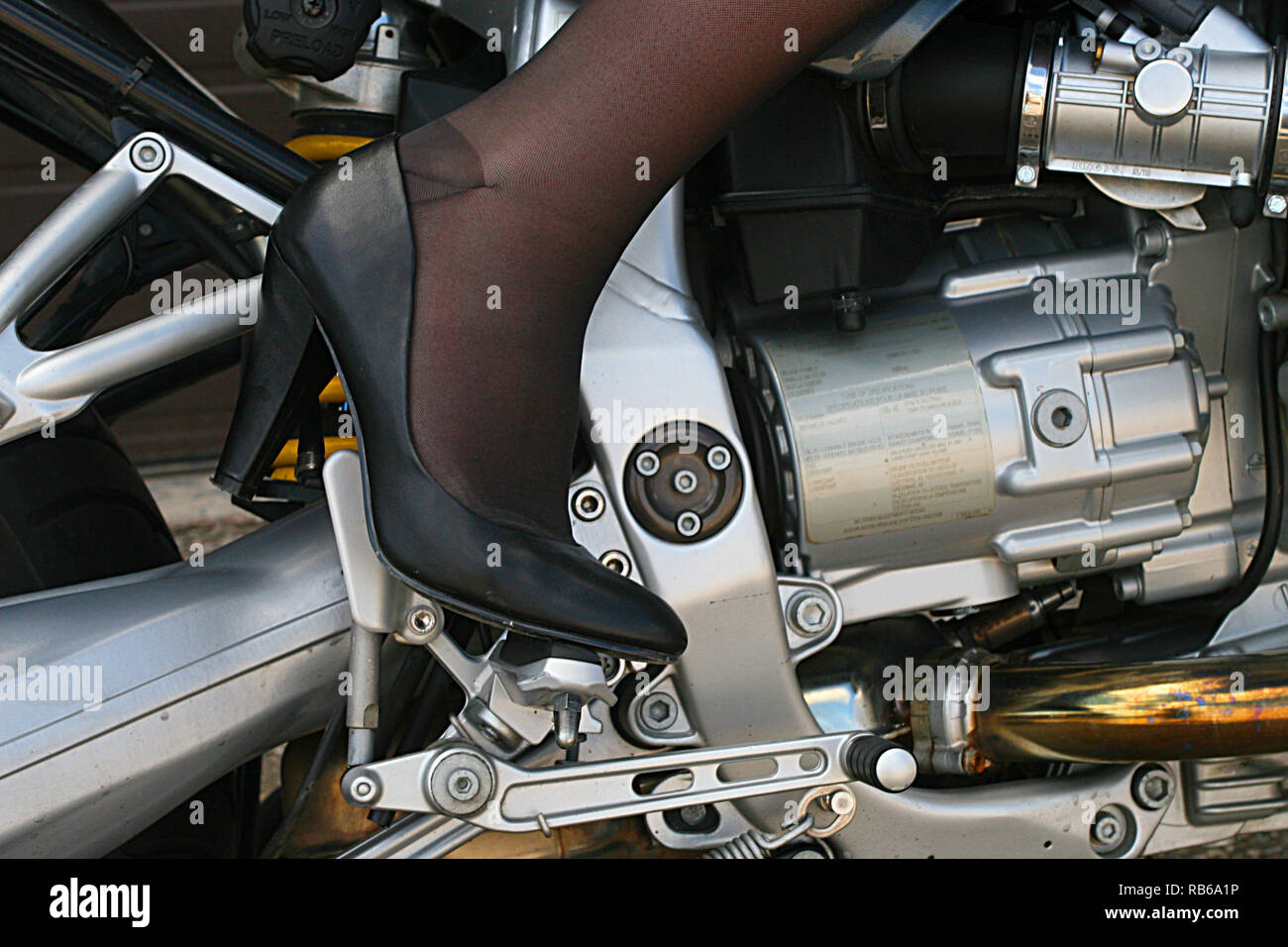 Blonde  Woman  wearing nylon stocking, high heels and short shorts riding a motorcycle - Stock Image