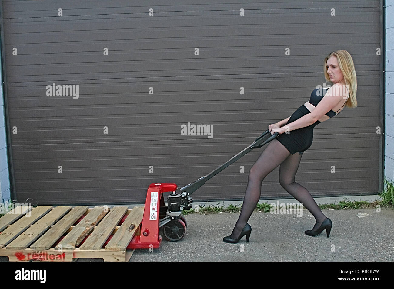 Blonde  Woman  wearing nylon stocking, high heels and short pushing a wheel barrow - Stock Image
