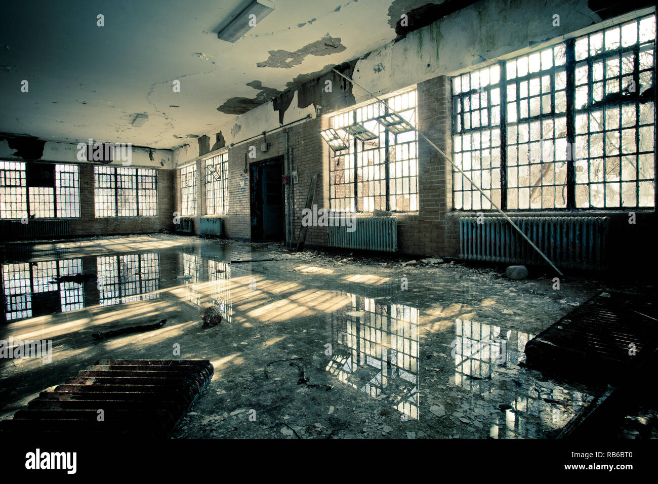 Interior of abandoned mental hospital with broken windows and water flood on floor Stock Photo