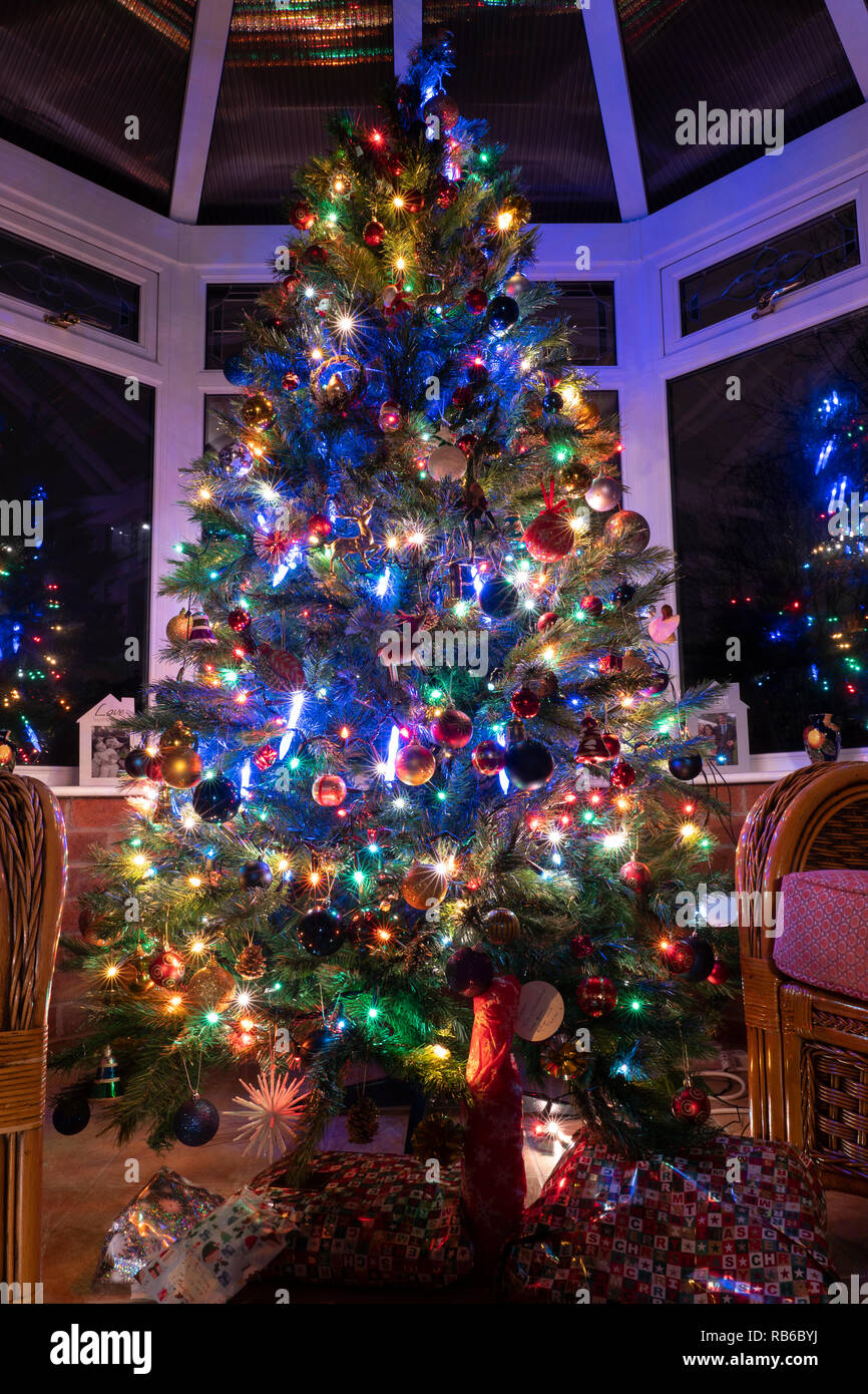 A Christmas Tree At Night In A House Conservatory With Presents Below Covered In Decorations And Illuminated By Lights Uk