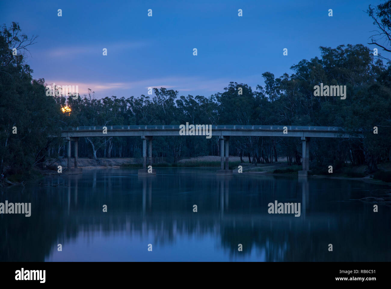 The sun just starting to rise over the Murray River, rural Australia, with cool tomes and reflections in the river Stock Photo