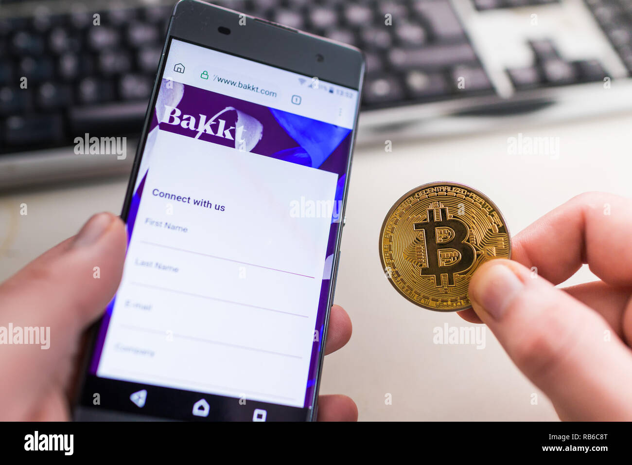 SLOVENIA - JANUARY 8, 2019: Man holding Bitcoin coin and in other hand smartphone with opened Bakkt website. - Stock Image