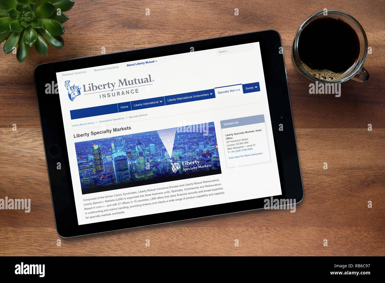 The website of Liberty Mutual insurance is seen on an iPad tablet resting on a wooden table (Editorial use only). - Stock Image