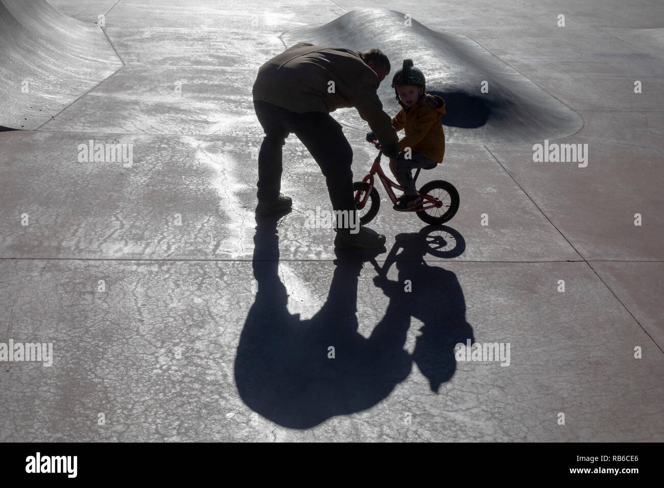 Denver, Colorado - Adam Hjermstad Sr. helps his four-year-old son, Adam Jr., to ride his balance bike in a skatepark. - Stock Image