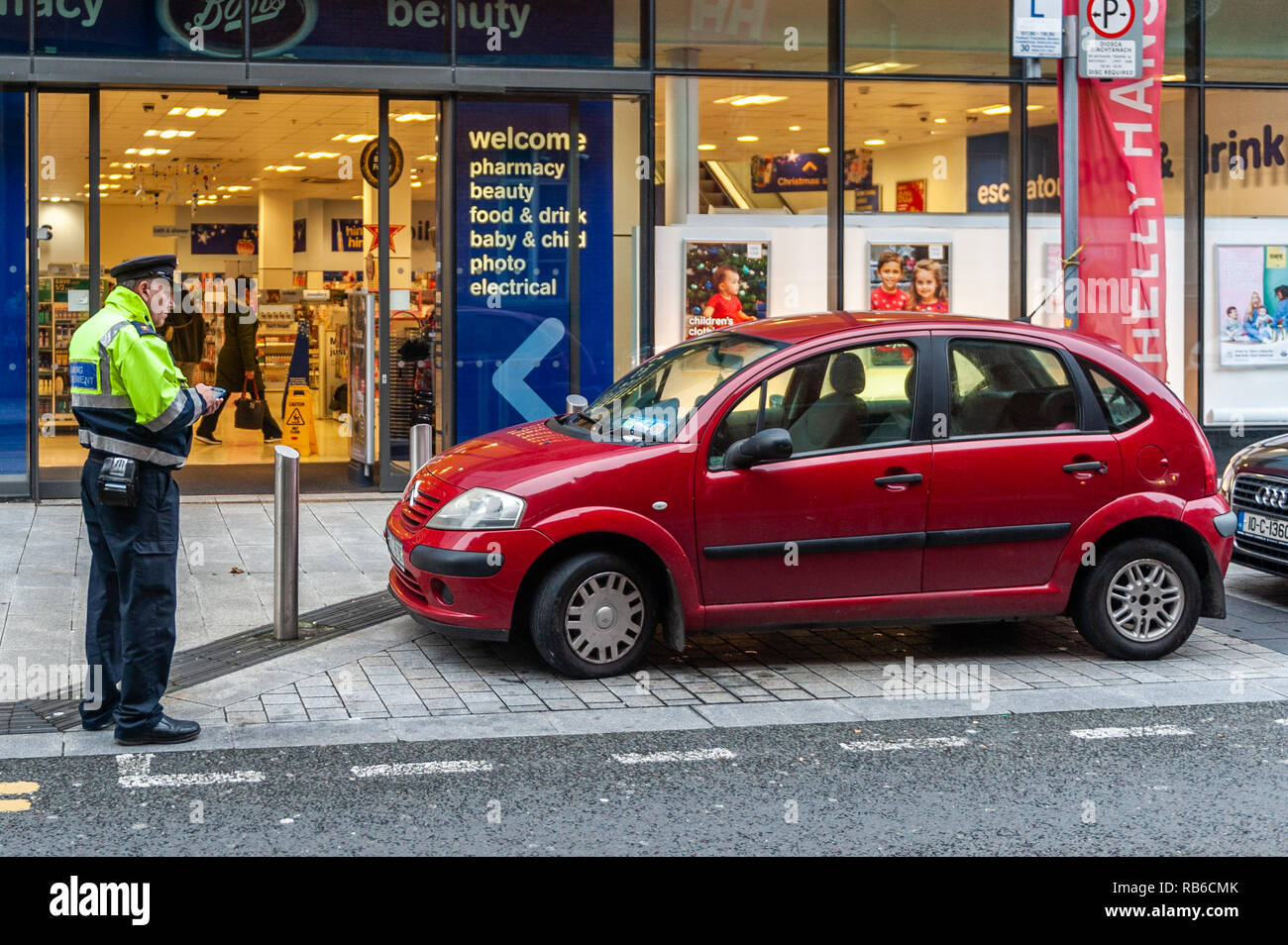 Traffic Warden/Parking Enforcer issues a ticket to an illegally parked car in Cork City, Ireland. - Stock Image