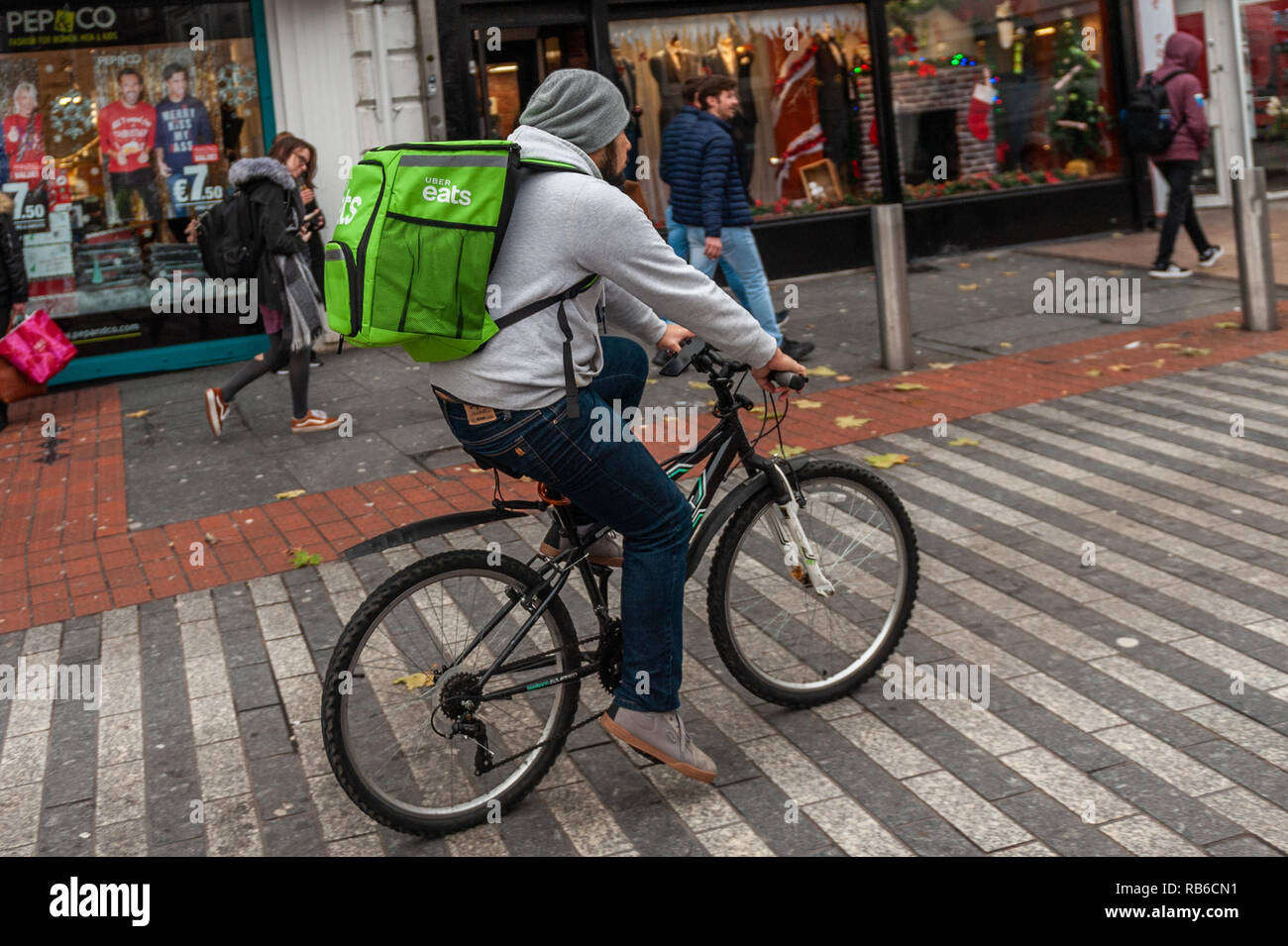 Uber Eats bike courier delivering food in Cork City, Ireland. - Stock Image