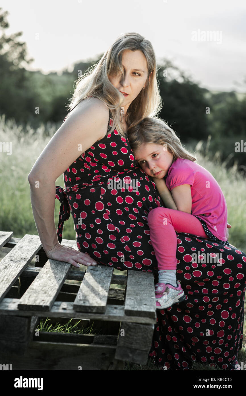 Crying girl looking for comfort nestled on her pregnant mother's belly - Stock Image