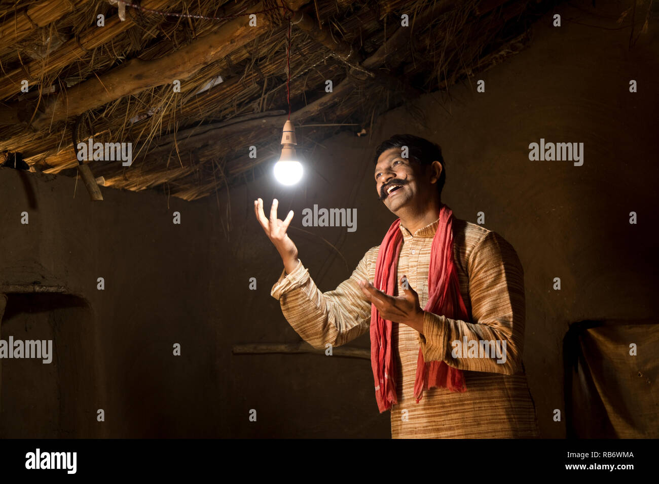 Rural Indian man delighted at the glow of light bulb and electricity reaching his home after long wait - Stock Image