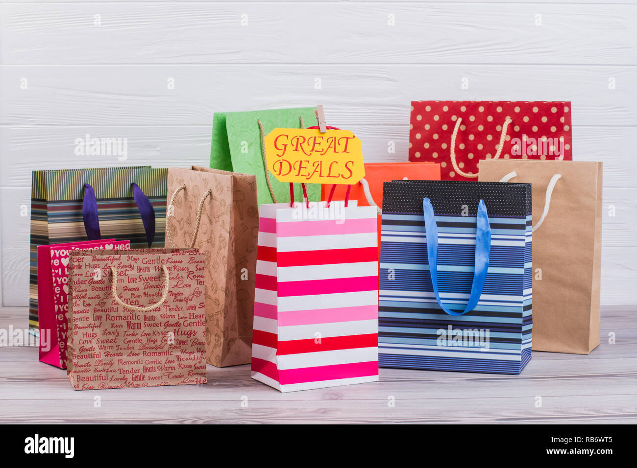 Various paper shopping bags. Group of gift bags with different printing and yellow card with inscription great deals. Commerce, marketing and lifestyl - Stock Image