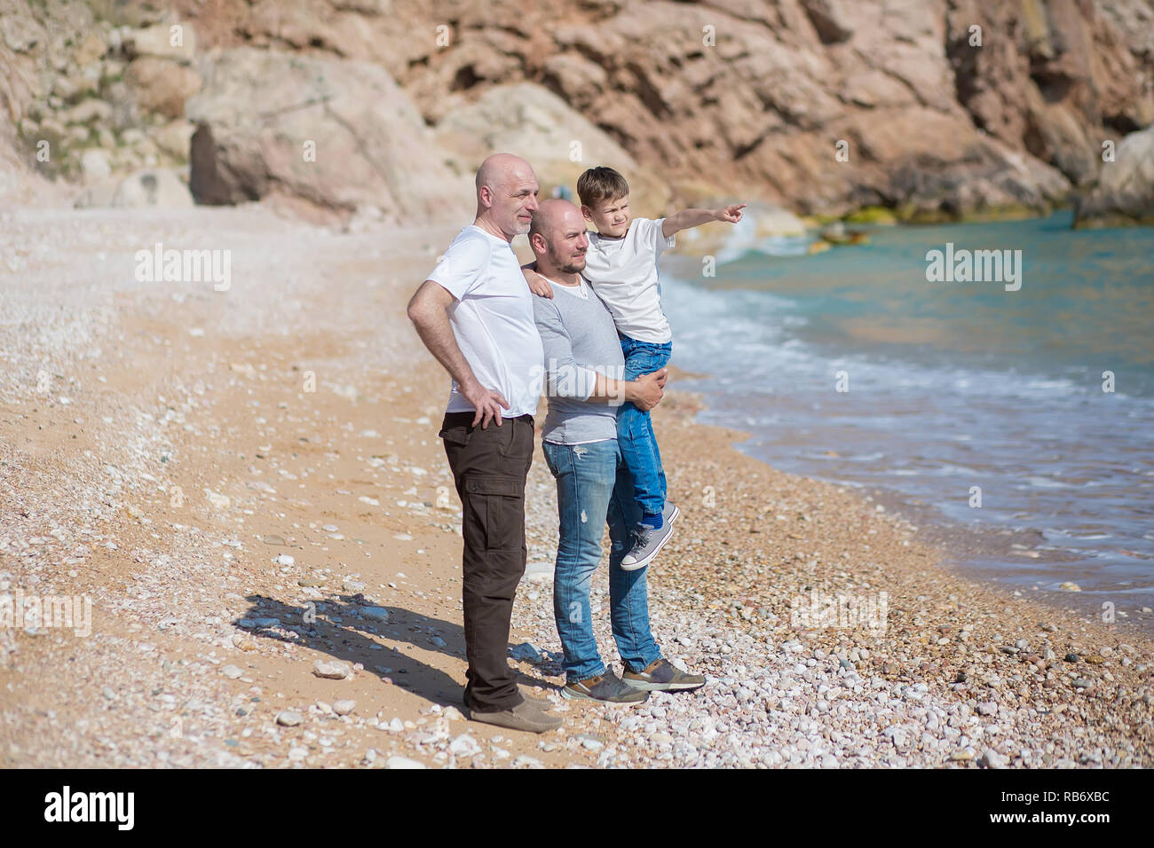 Family of grandfather father and son on a rocky beach on vacation enjoying time together. - Stock Image