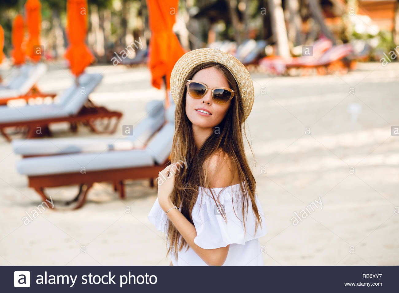 Cute girl in brown sunglasses and straw hat smiles charmingly. She wears  white short dress with open shoulders. She sits on a beach chaise-longue  and plays ... 442a5c9a392