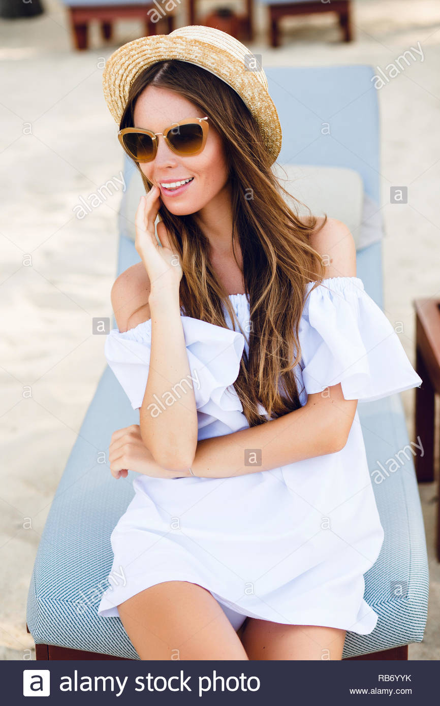 Cute girl in brown sunglasses and straw hat smiles widely and holds her  hand near chin. She wears white short dress with open shoulders. She sits  on a beach ... 1f2f7ff78e7