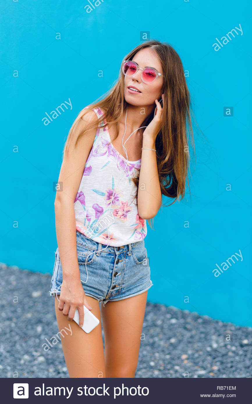3f7e8fa32a Cute stylish girl on blue background stands and listens to music on  earphones on smartphone.