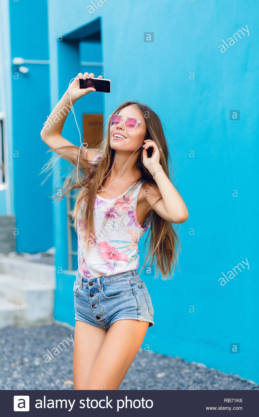 4240e5a807 Cute stylish girl on blue background dances and listens to music on  earphones on smartphone.