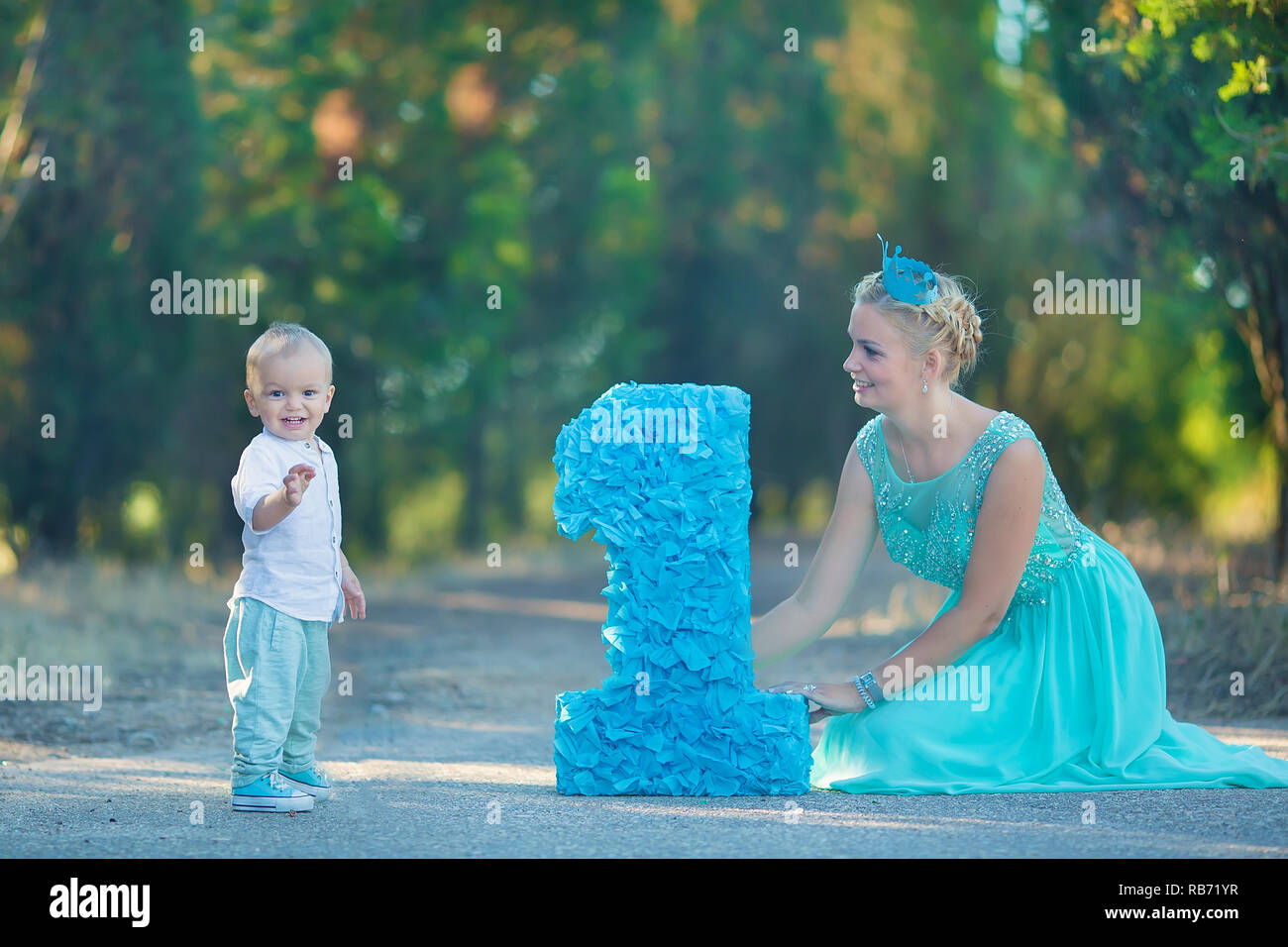Beautifull Mother Lady Mom In Stylish Blue Dress Together With Her Son And Number One Birthday Park