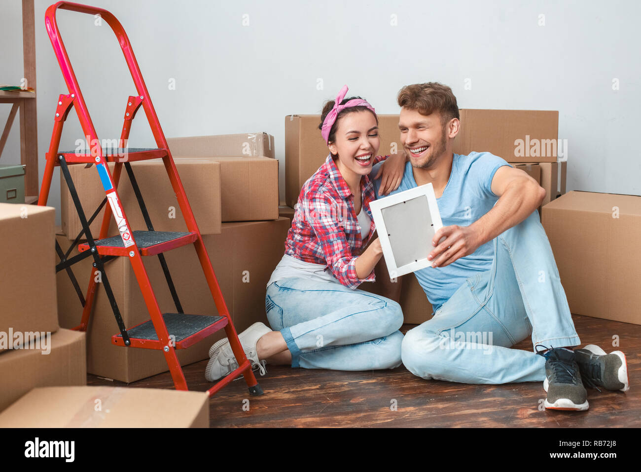 Young Husband And Wife Moving To New Place Sitting On Floor Hugging