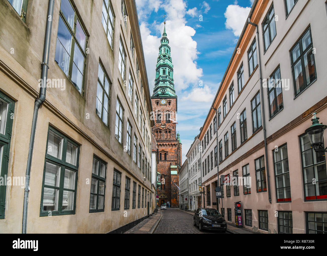 The clock tower of the St Nicholas Church is seen from a nearby street on a summer day in Copenhagen, Denmark. - Stock Image