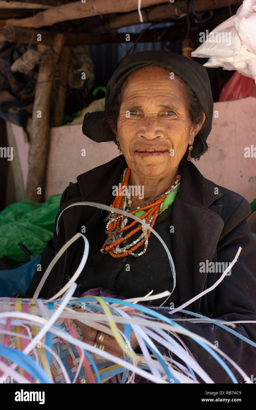 An elderly woman weaves a basket made from torn up strips of plastic/hessian.  She has poor teeth due to chewing betel nut and so does not smile. - Stock Image