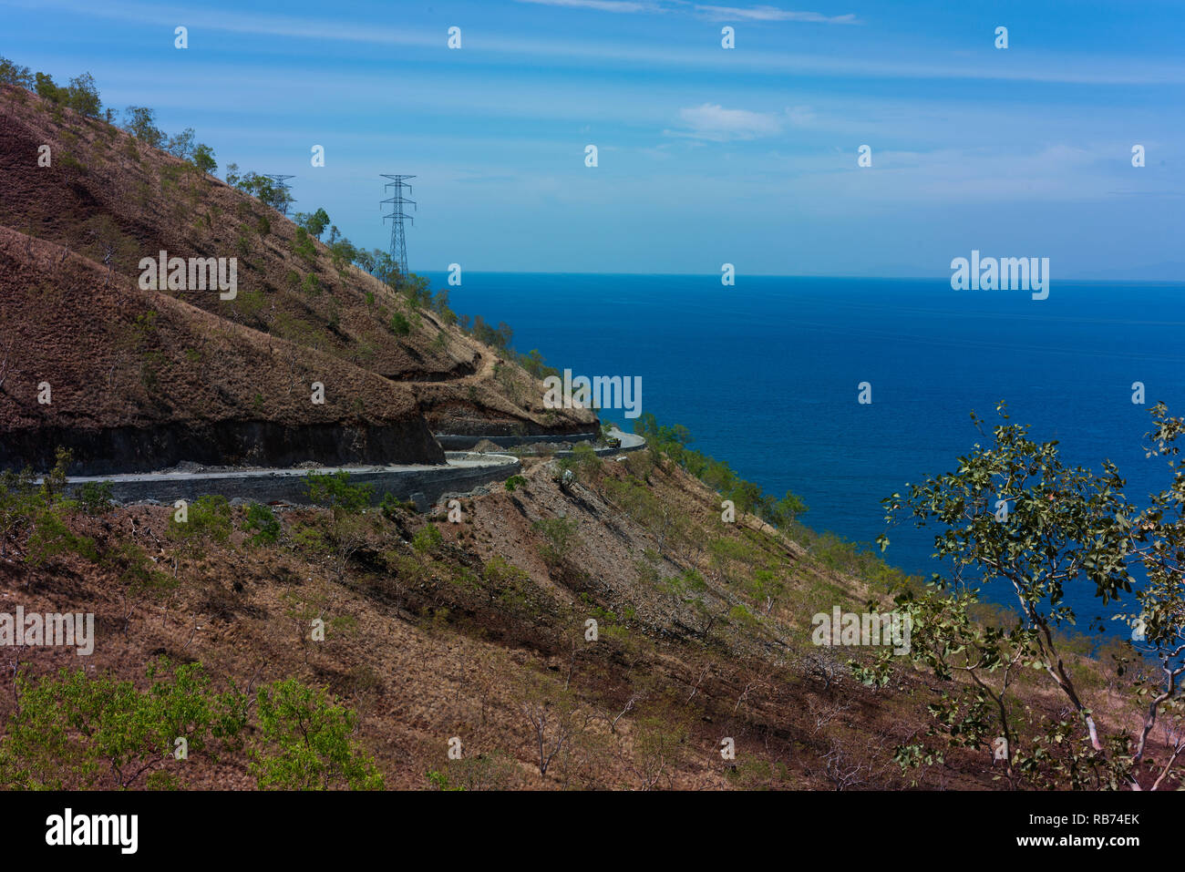A newly constructed road on the north coast of Timor Leste at the end of the dry season. - Stock Image