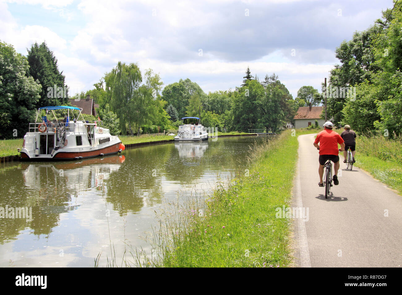 Men cycling along the Canal de Bourgogne by bike in the Burgundy region of France in the French countryside - Stock Image