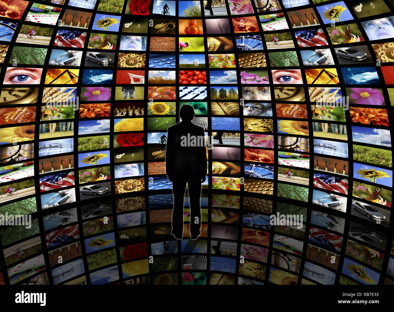 spherical room with a wall of television screens and a man standing on a reflective floor looking at it - Stock Image