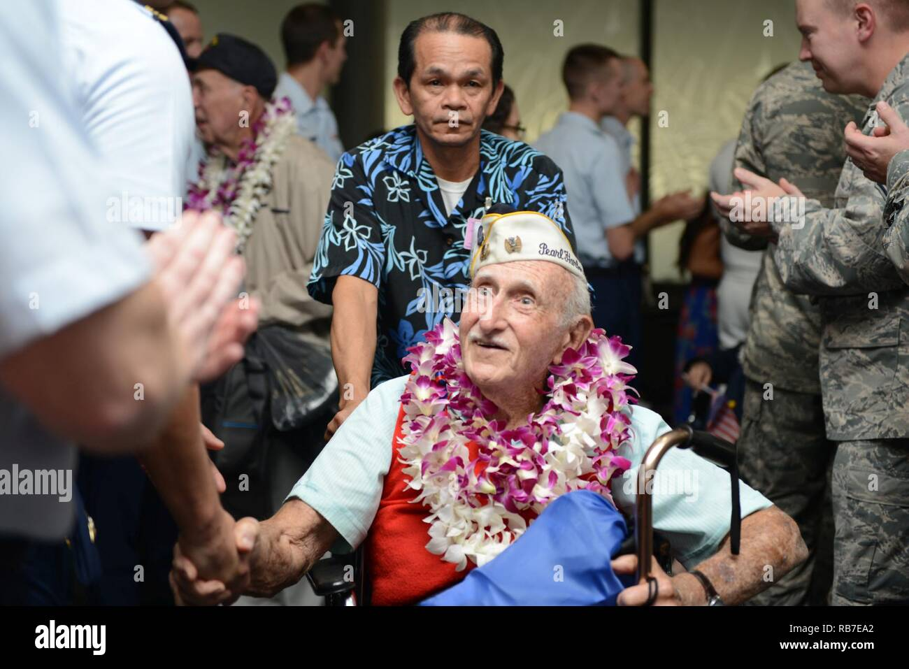 a pearl harbor survivor is greeted by several military members and