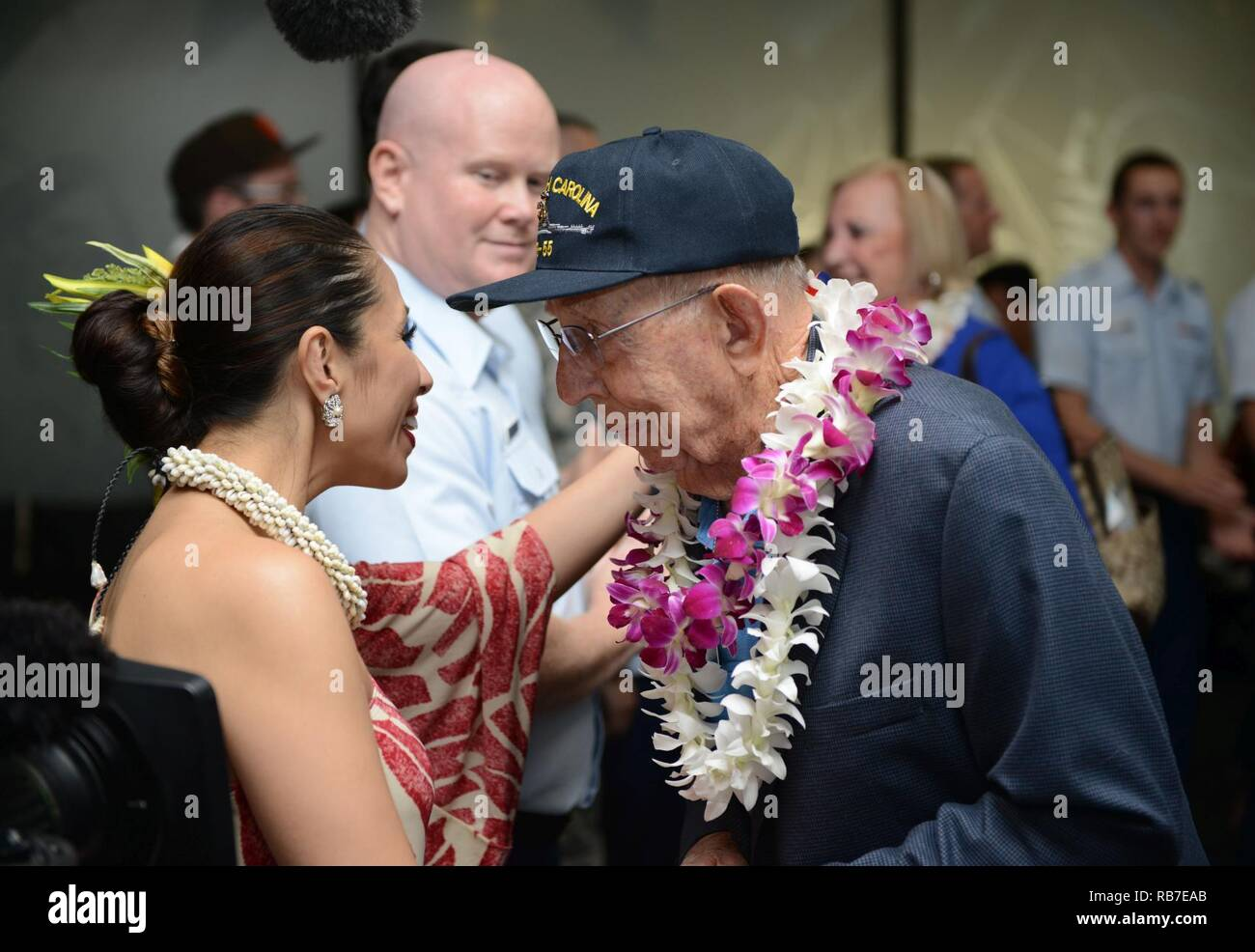 a world war ii veteran shakes hands with personnel and military