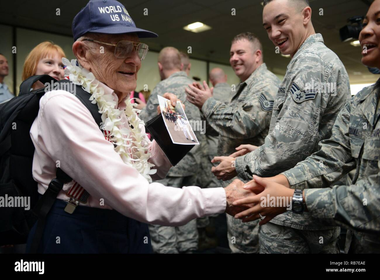 a world war ii veteran shows a photo of himself to several military