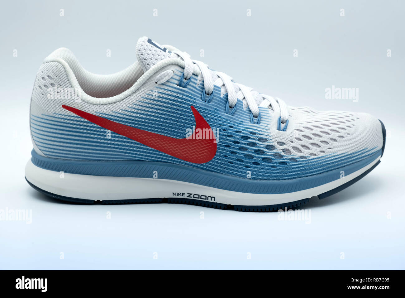 10862ba8 Lateral view of a blue and white Nike Pegasus 34 trainer with a red swoosh  logo