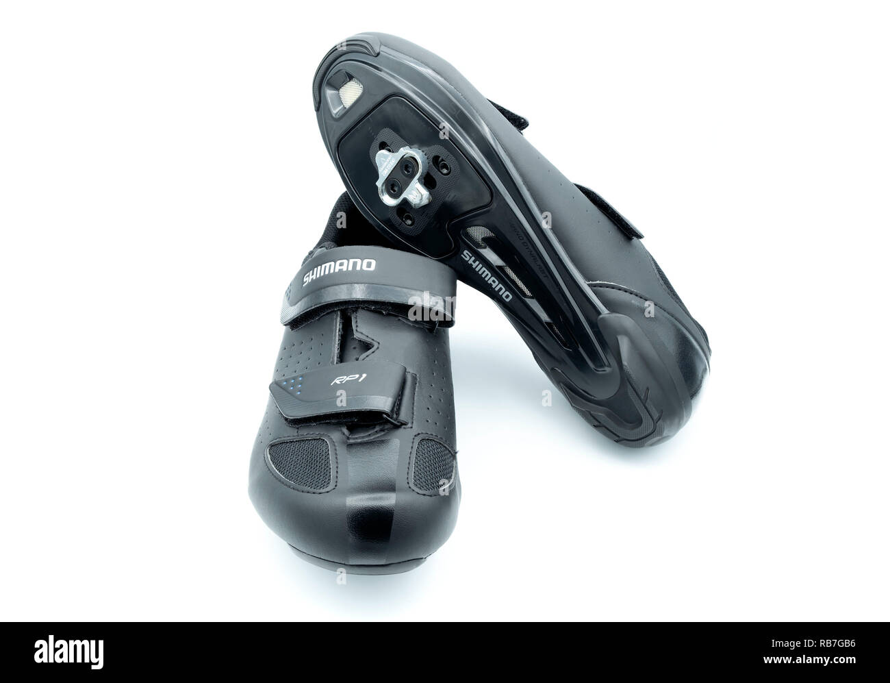 Pair of black Shimano road cycling / spinning class shoes with clipless cleats cut out isolated on white background - Stock Image