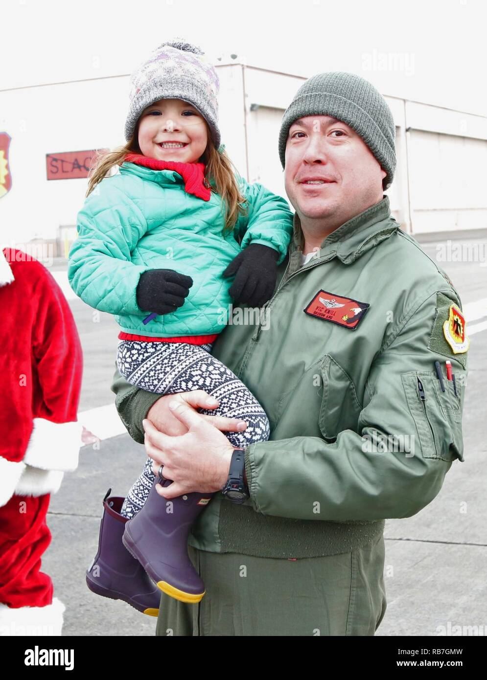U.S. Air Force Major Vic Knill, and his daughter smile after seeing Santa Clause arrive in an F-15 Eagle during the 173rd Fighter Wing's annual Children's Christmas party at Kingsley Field in Klamath Falls, Ore. Dec. 4, 2016. Santa's arrival in the F-15 was the highlight of the event held for members of the base and their families, and featured games, face painting, hot cocoa, and pictures with Santa and Mrs. Clause. - Stock Image