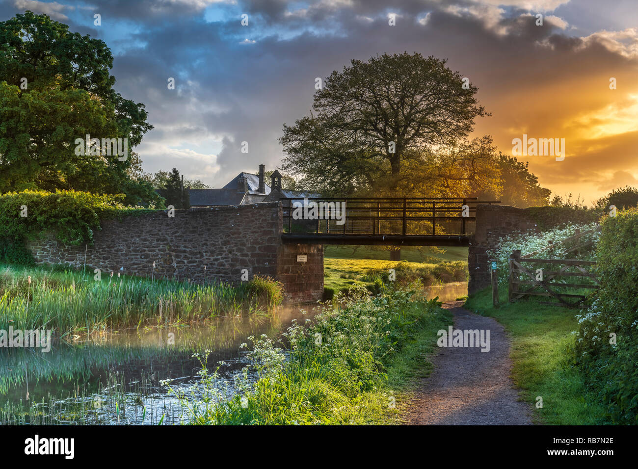 UK Weather - After a night of heavy showers, the sun rises behind Ayshford Brige on the Great Western Canal near Samford Peverell in Devon. - Stock Image