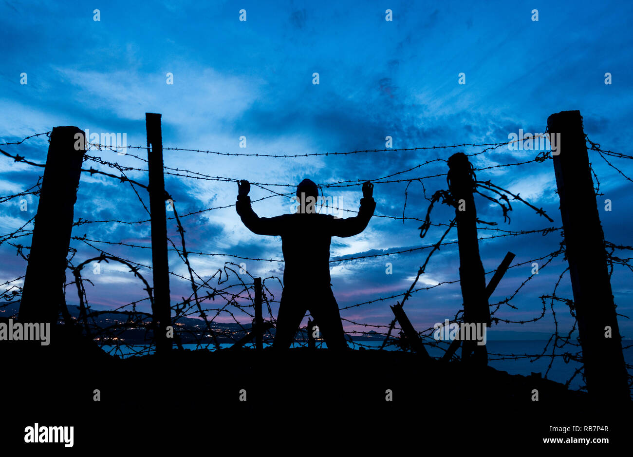 silhouette of man looking through barbed wire/ razor wire fence at night. Brexit, immigration, asylum... concept - Stock Image