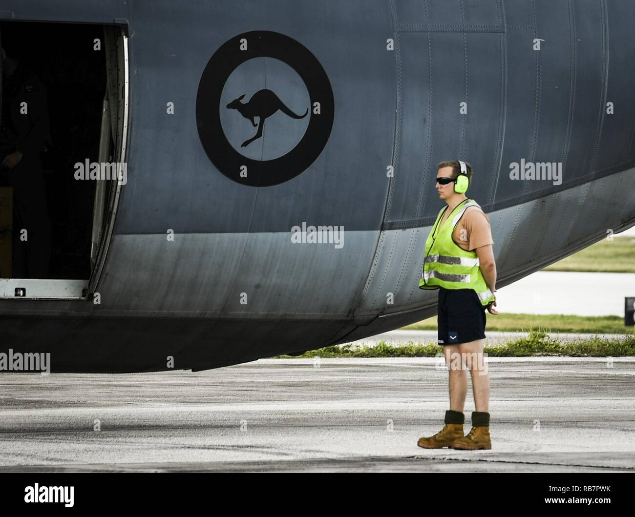 A maintainer with the Royal Australian Air Force waits to marshal a C-130J Super Hercules for takeoff during Operation Christmas Drop at Andersen Air Force Base, Guam, Dec. 7, 2016. The RAAF sent a C-130J to OCD to train with the 36th Airlift Squadron and the Japan Self Defense Force, helping participants understand each other's techniques and giving them a chance to offer each other insight. Bilateral training improves participants's abilities to work together during real world scenarios, such as delivering disaster relief supplies. - Stock Image