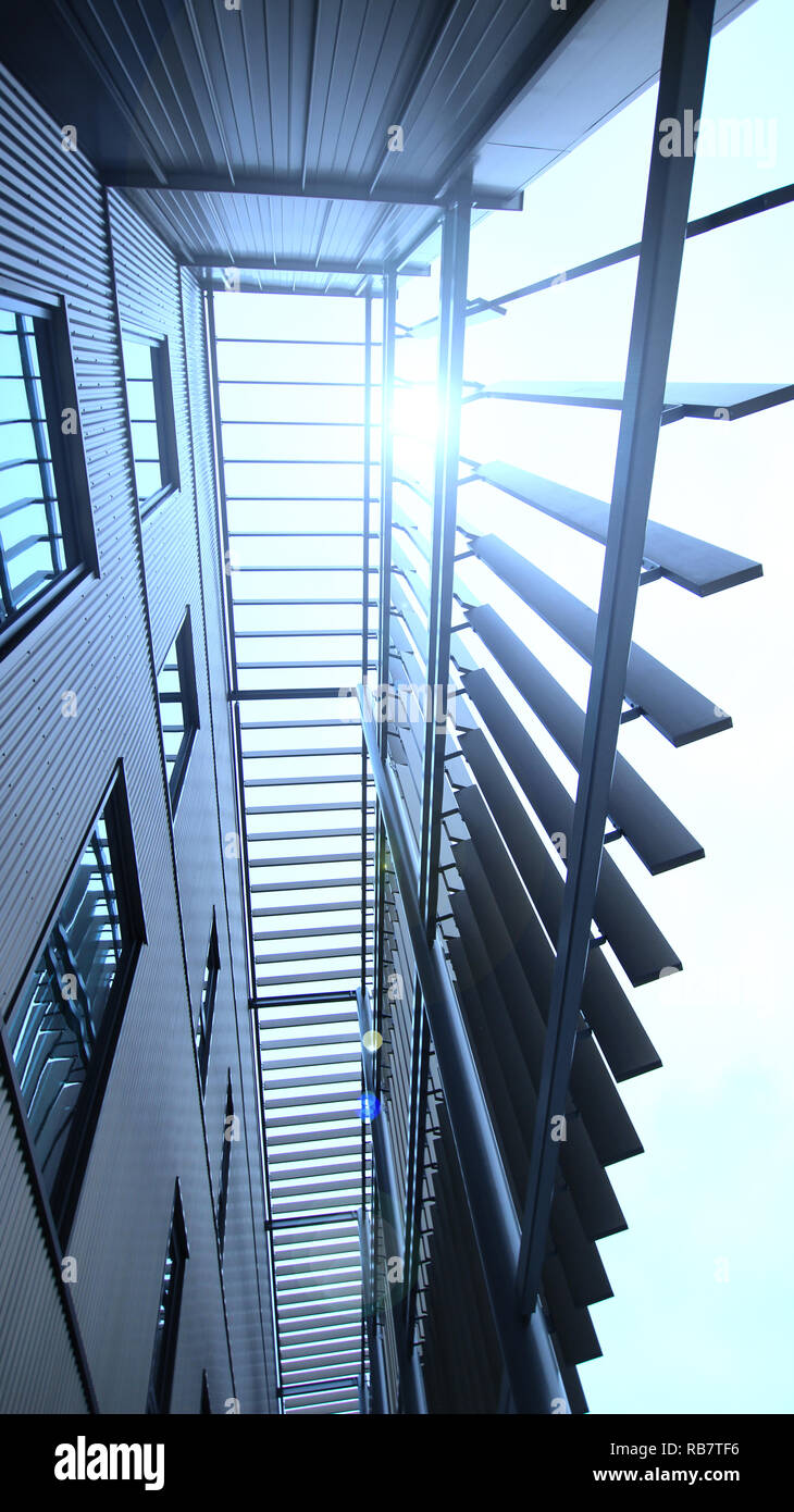 Modern building exterior feature, shot from a low angle with windows reflecting the long slats for aesthetic value and creative use of light. - Stock Image