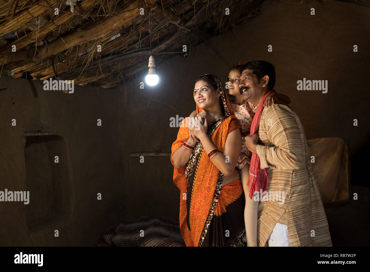 Rural Indian family delighted at the glow of light bulb and electricity reaching their home after long wait - Stock Image