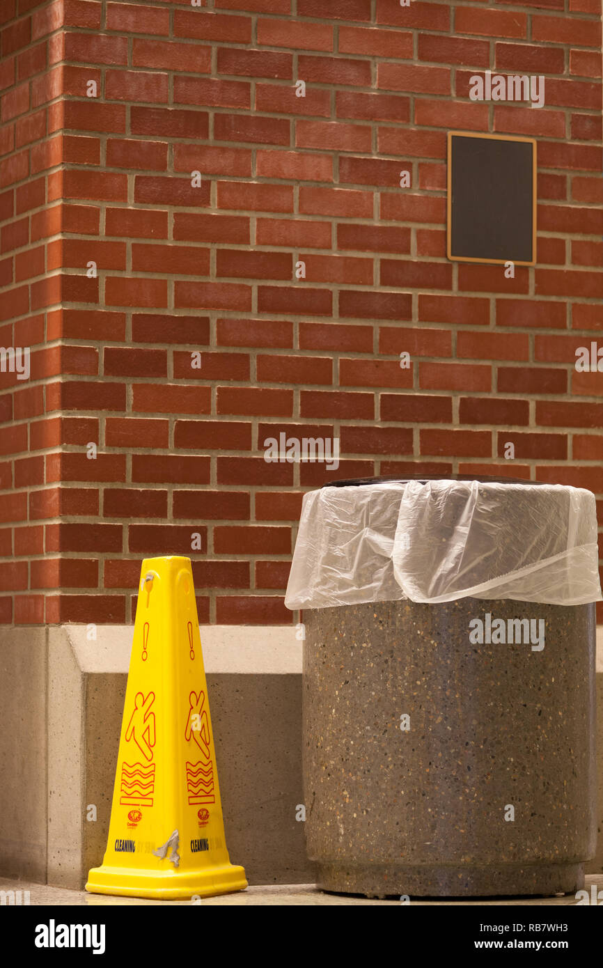 Garbage container and a wet floor marker against a red brick wall - Stock Image