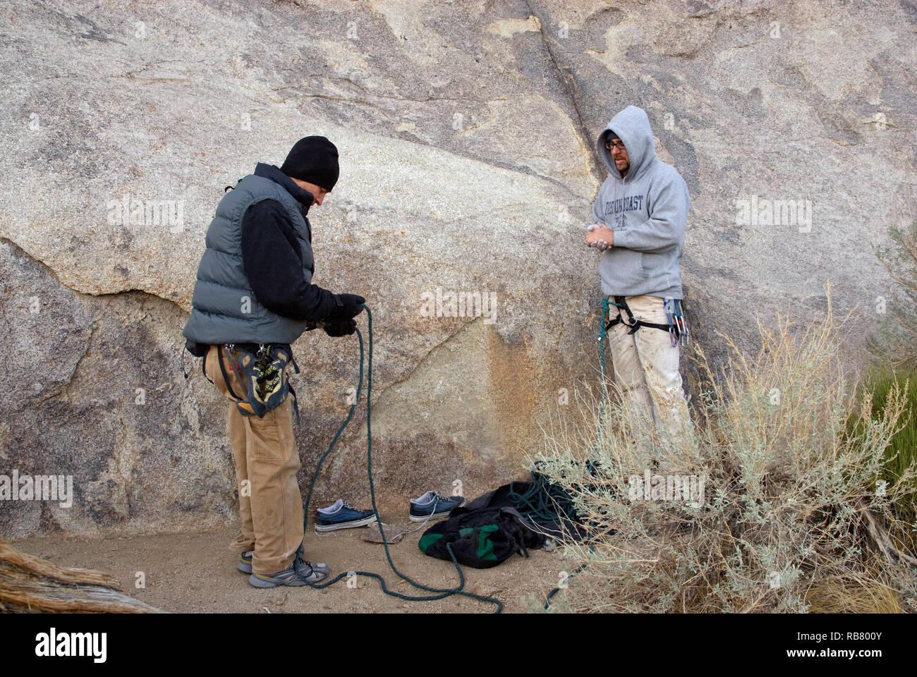Rock climbers preparing to climb a rock on cold winter morning in Alabama Hills near Lone Pine in Eastern Sierra Nevada, California, USA - Stock Image