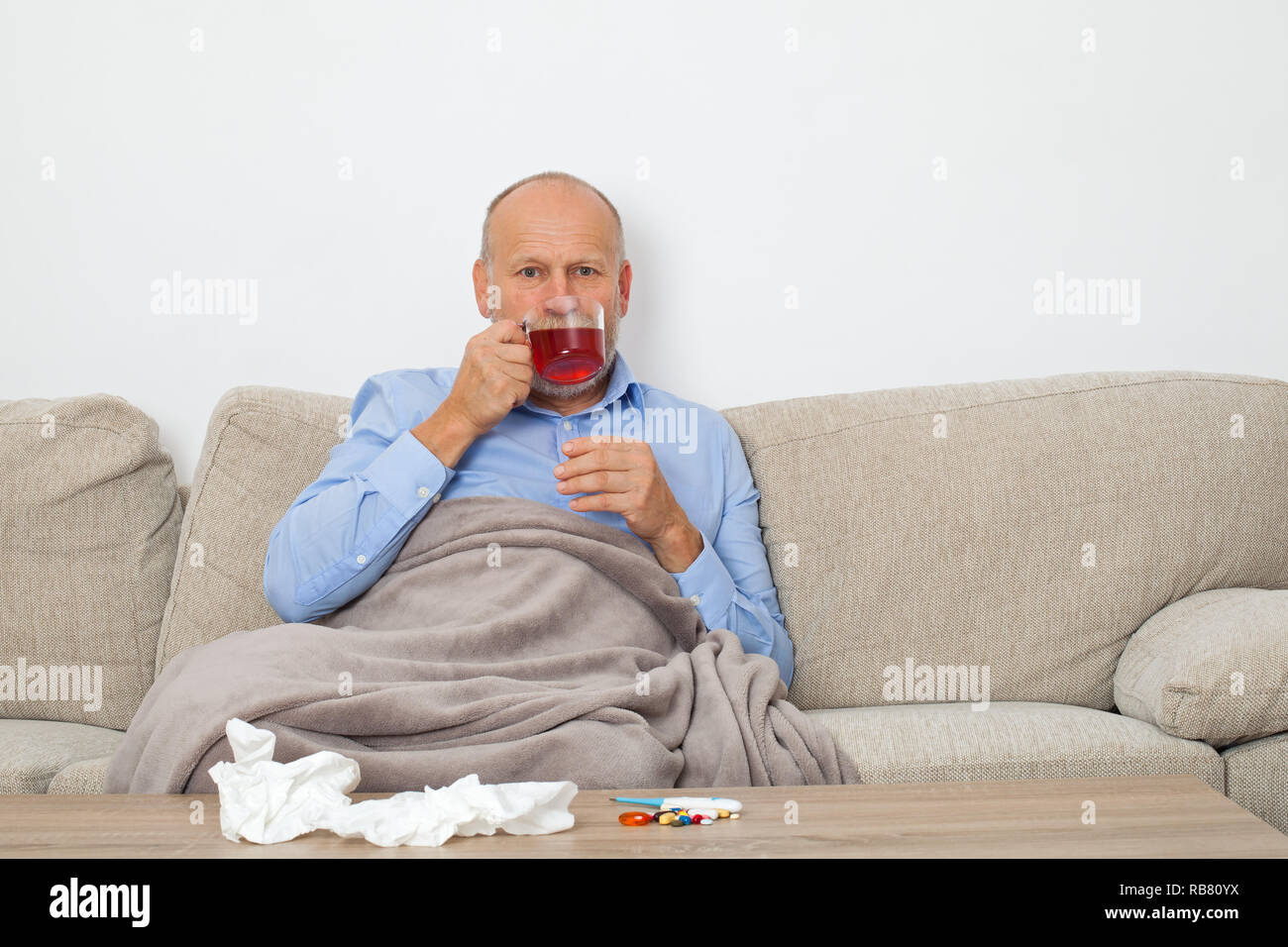 Senior man with seasonal influenza sitting on the couch, wrapped in a blanket and drinking hot tea - Stock Image