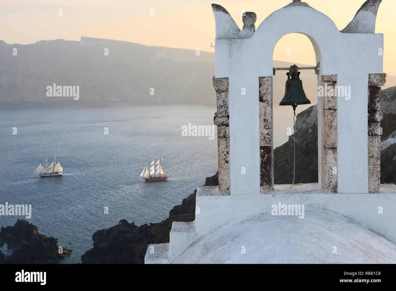 City of Oia on Santorini Island. View onto church with bell built on the volcano rim (Caldera). Sailing ships on the Mediterranean Sea below - Stock Image