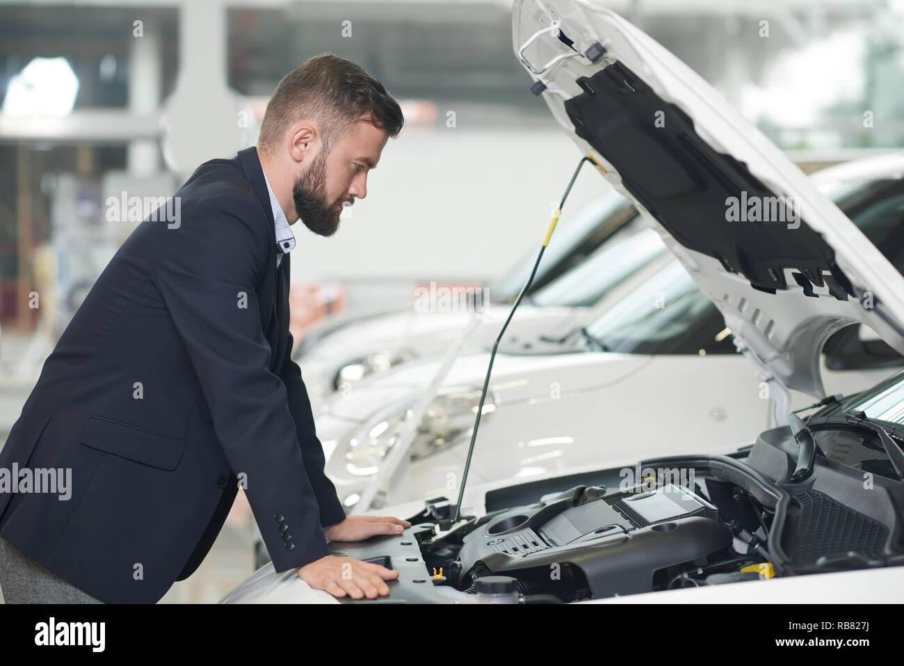 Male client of car center observing vehicle in showroom. Man leaning on white car with opened hood and looking under hood. Concentrated customer wearing in dark blue jacket. - Stock Image