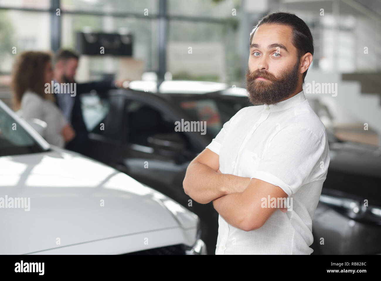 Brutal, bearded man standing, looking at camera. Man in white shirt posing in car dealership. Handsome client of car center. Background of car showroom with different vehicles. - Stock Image