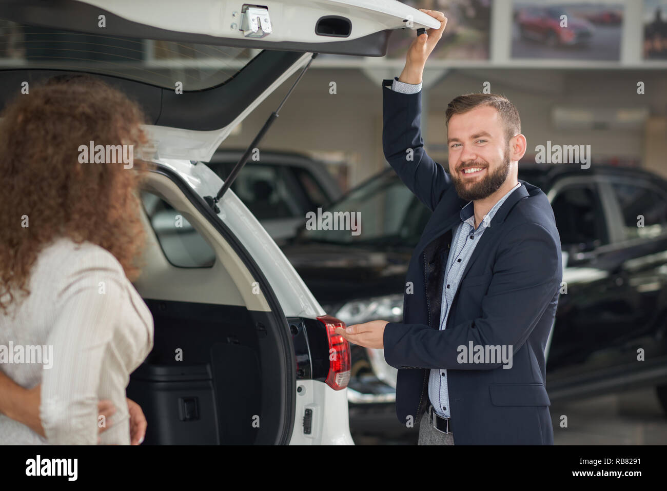 Car dealer showing luggage space to female client. Woman observing details of vehicle, checking quality. Handsome bearded manager smiling, looking at camera, holding hand on auto. - Stock Image