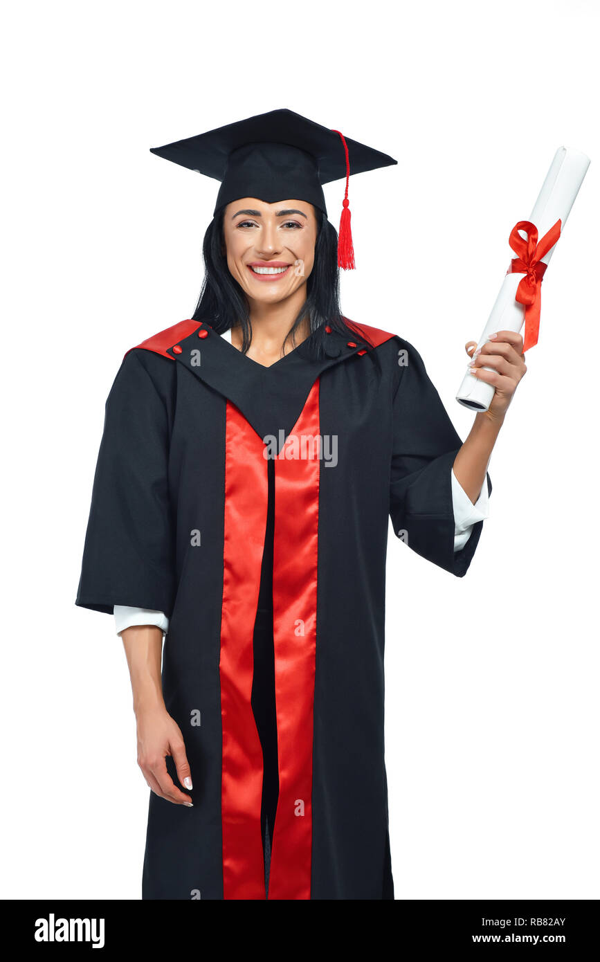 Portrait of happy alumni of university on white background. Young lady in black and red academical dress and square academic cap posing at camera. Girl holding diploma and celebrating graduation. - Stock Image